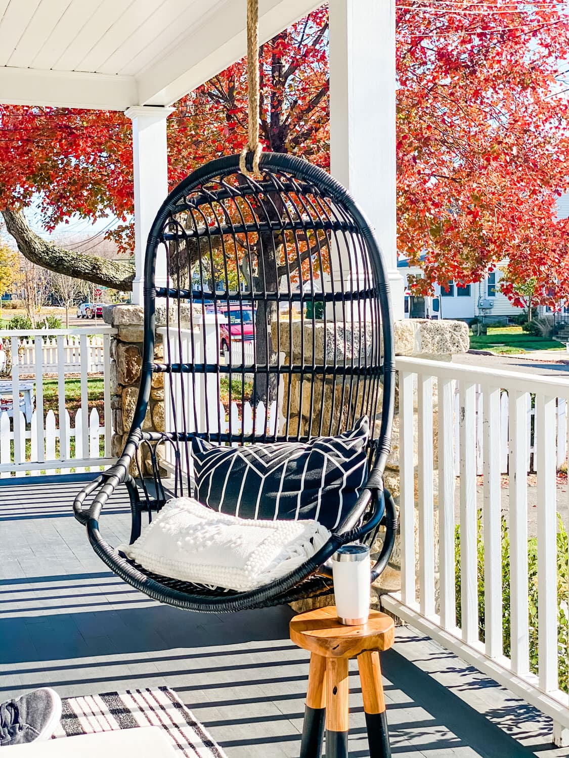 a black painted hanging chair on a porch with a tree in the fall with red leaves