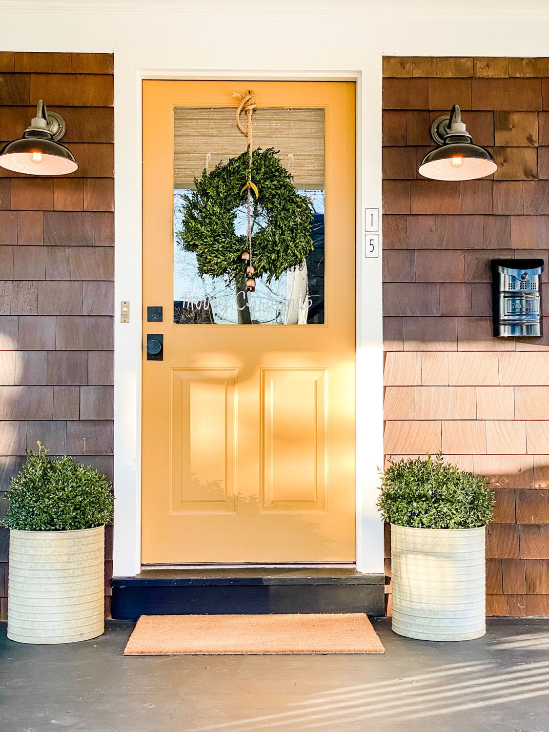 yellow door on shingled cottage with a boxwood wreath and planters