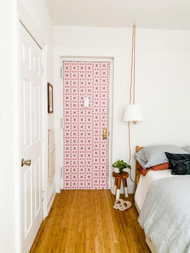 wallpaper on door, pendant lamp, stool, plant