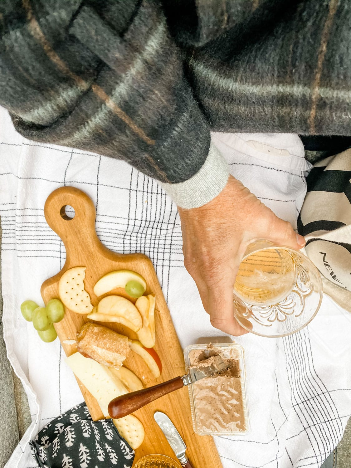 woman wearing a wool plaid coat holds a beer with a picnic