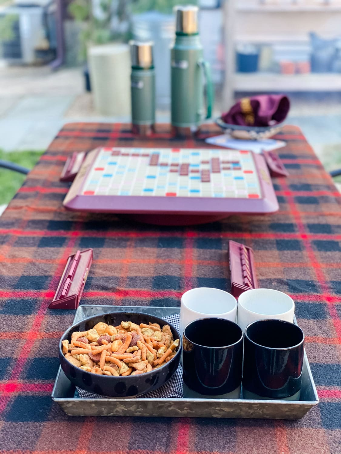 Stanley Thermos and scrabble piece bag on Pendleton blanket, black and white cups and bowl of snack mix