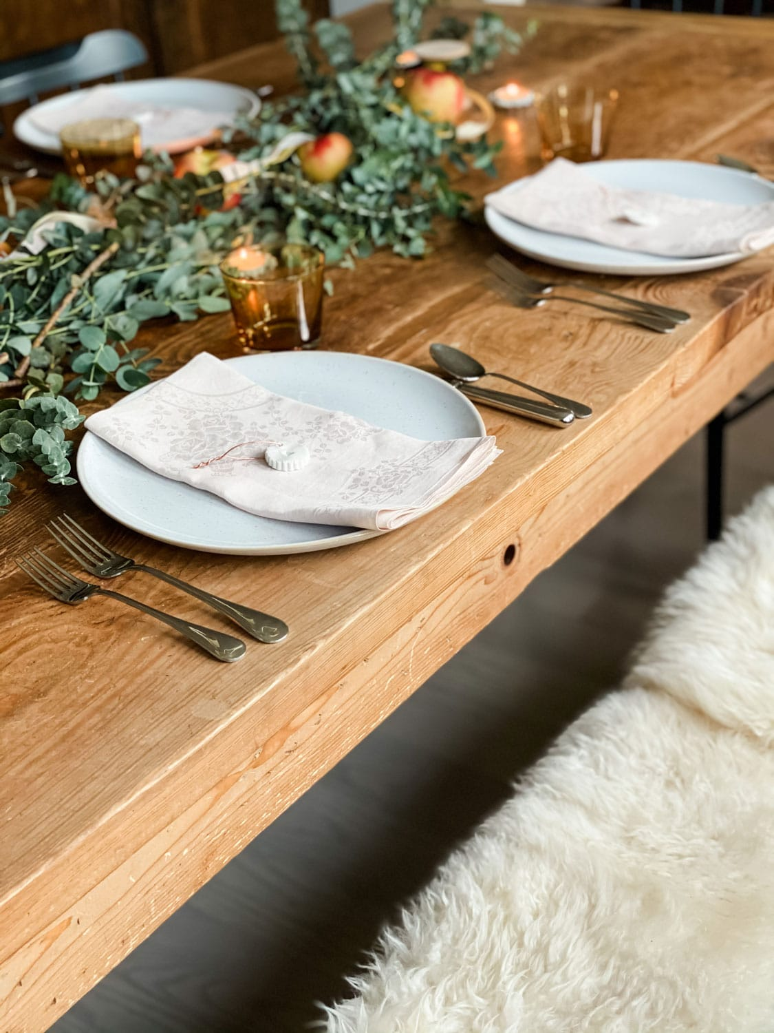 bench with sheepskins at a table set for thanksgiving