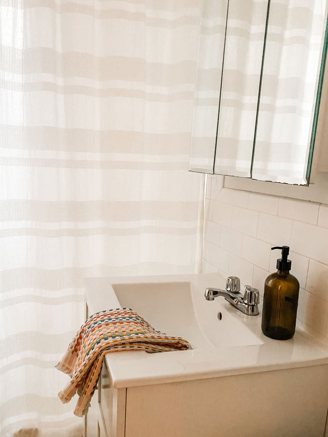 all white bathroom with soap bottle and towel