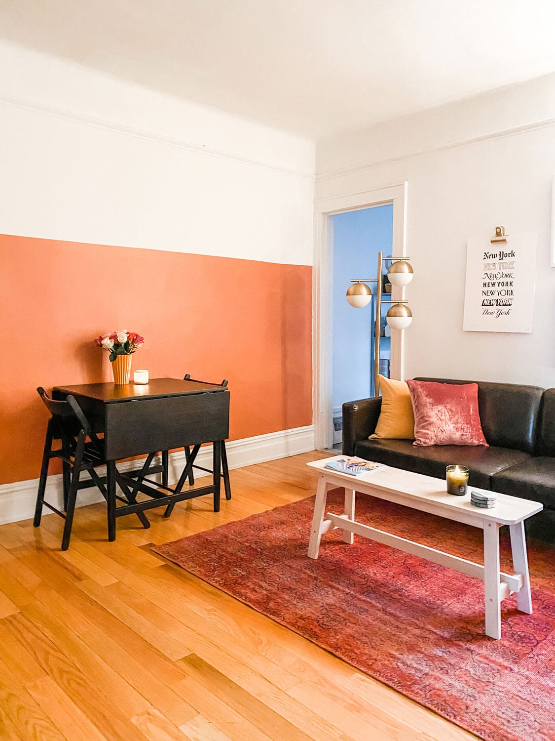 small black table and chairs against a pink half wall