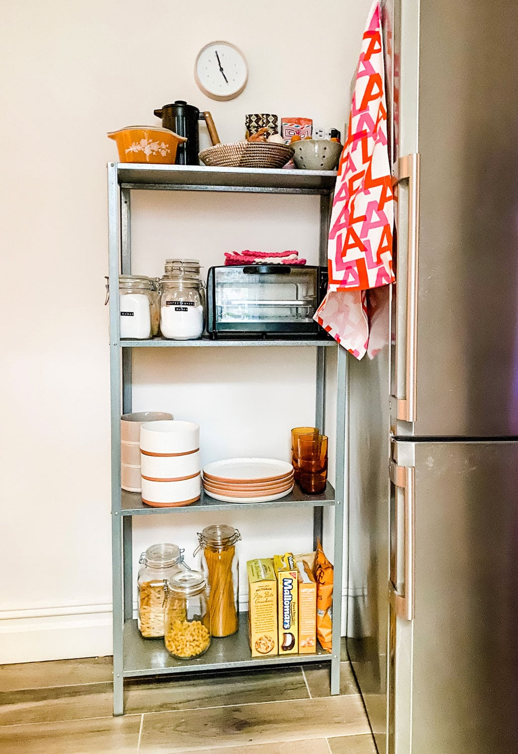 small open galvanized shelf in kitchen with dishes, toaster oven