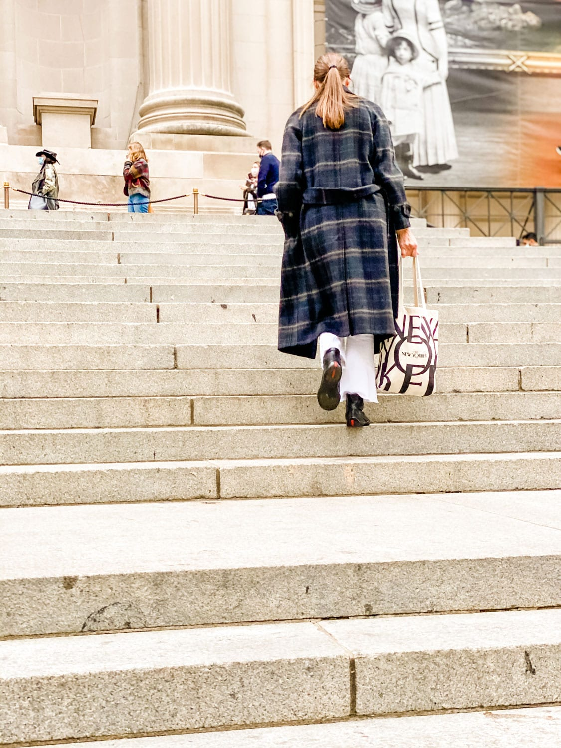 woman walking up the steps of The Met wearing a wool coat and holding a New Yorker tote