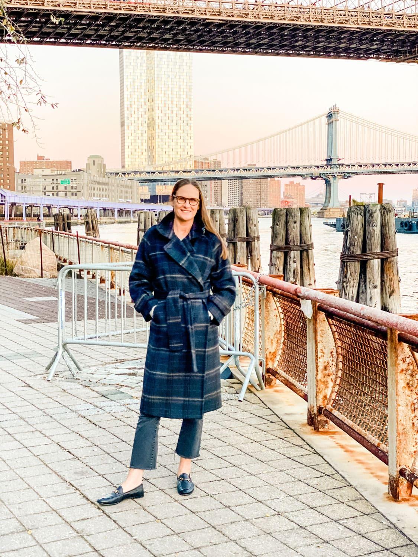 woman standing with Brooklyn bridge behind her