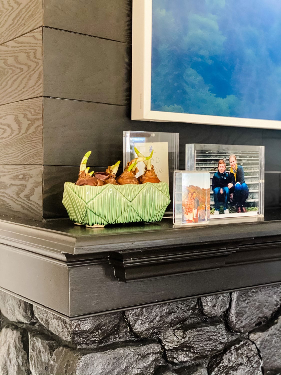 acrylic frames and paperwhotes in green McCoy pot on black stone fireplace mantel