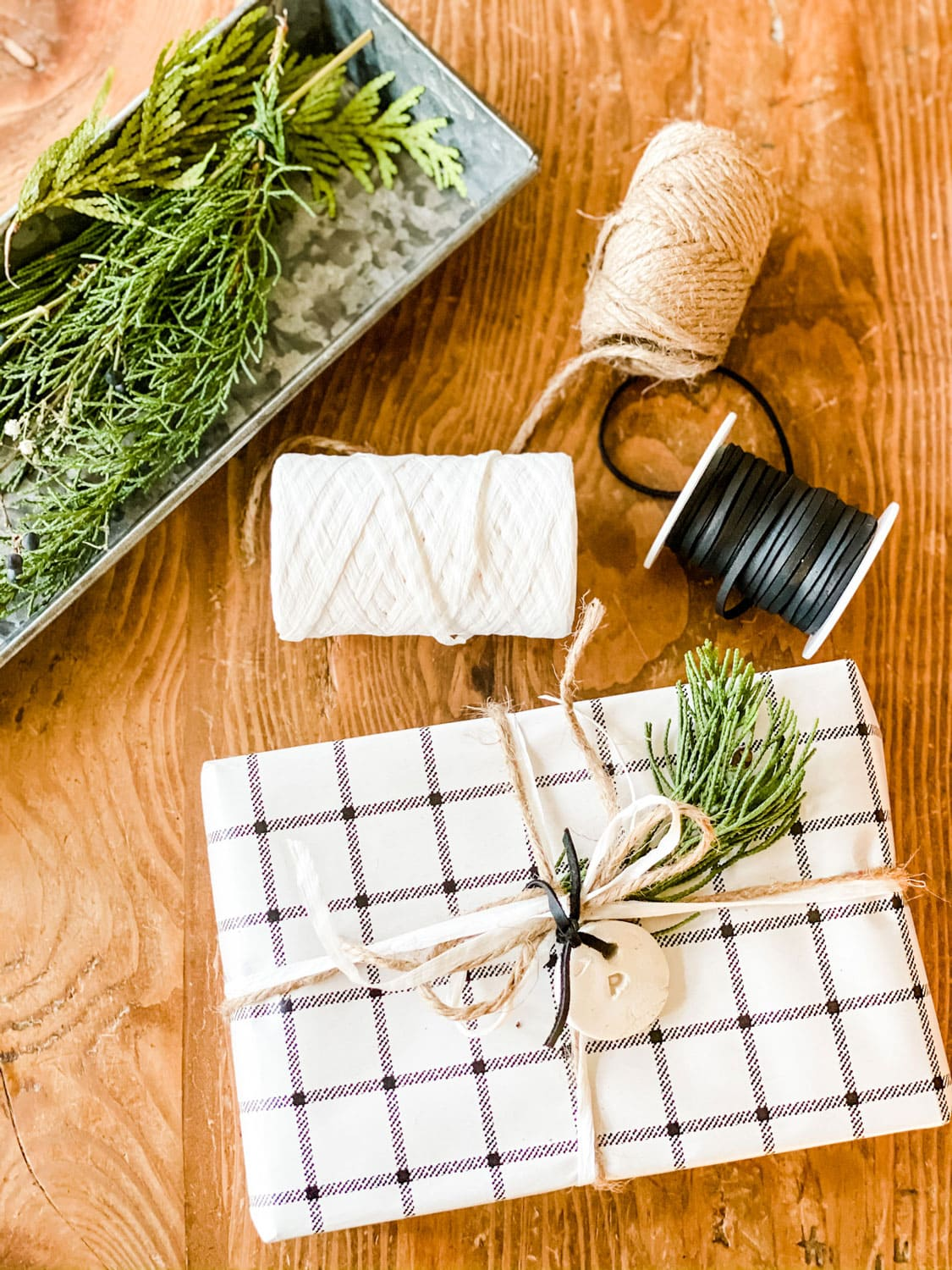 black and white gift wrap paper, twine, cord, fresh greens