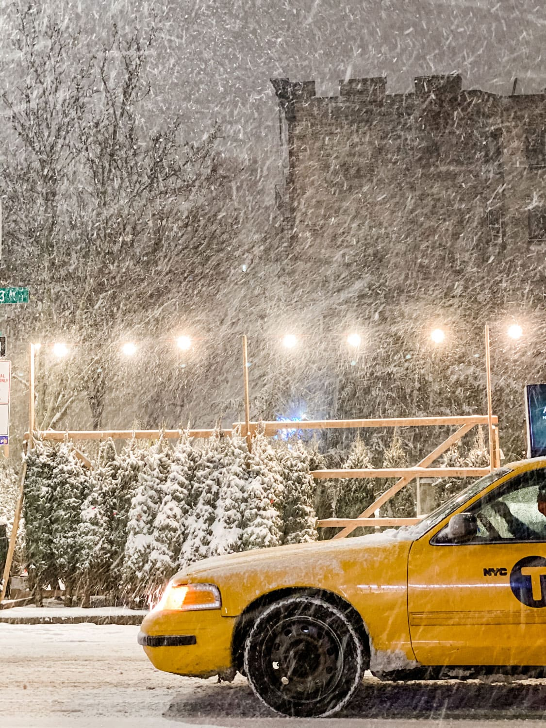 Lifestyle blogger Annie Diamond take in Christmastime in New York...a yellow taxi driving by a sidewalk tree stand in a snow storm feels slightly magical.
