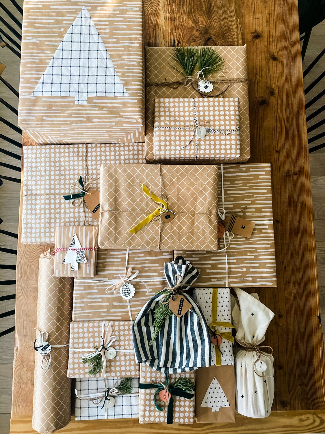 an assortment of gifts wrapped using Kraft paper, ribbons, tags, evergreens, twine