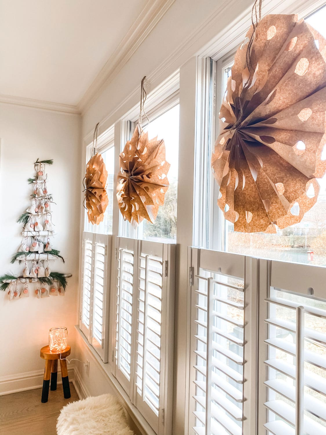 large paper bag snowflakes in windows