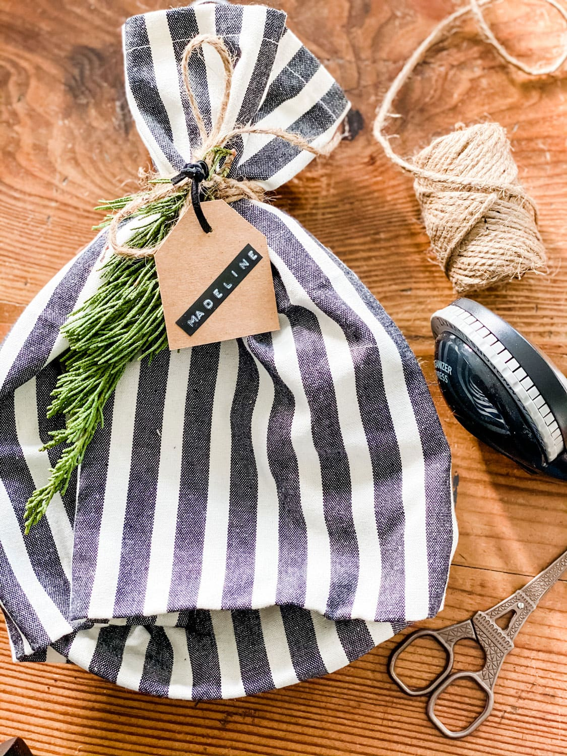 A black and white striped dish towel to wrap a gift with a tag and fresh greens