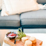 olive wood cutting board with crackers, herb sprig and small bowl of jam