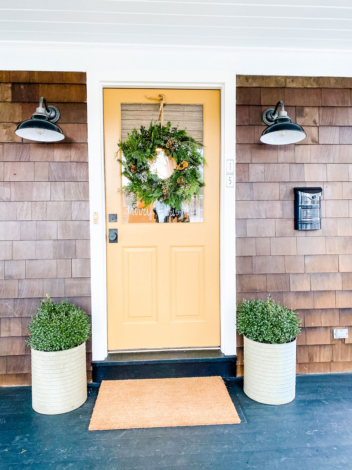 India yellow front door with planters and lights