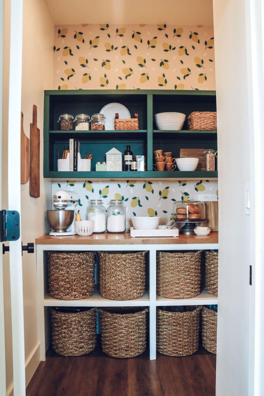 a pantry with lemon wallpaper and a green shelf, basket, jars