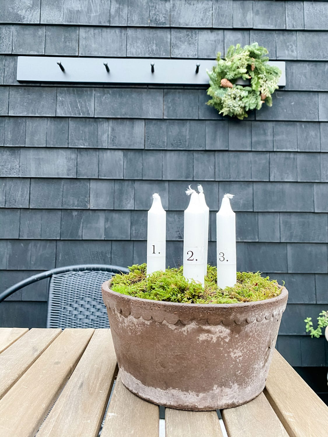 a shallow planter on table with candles and moss