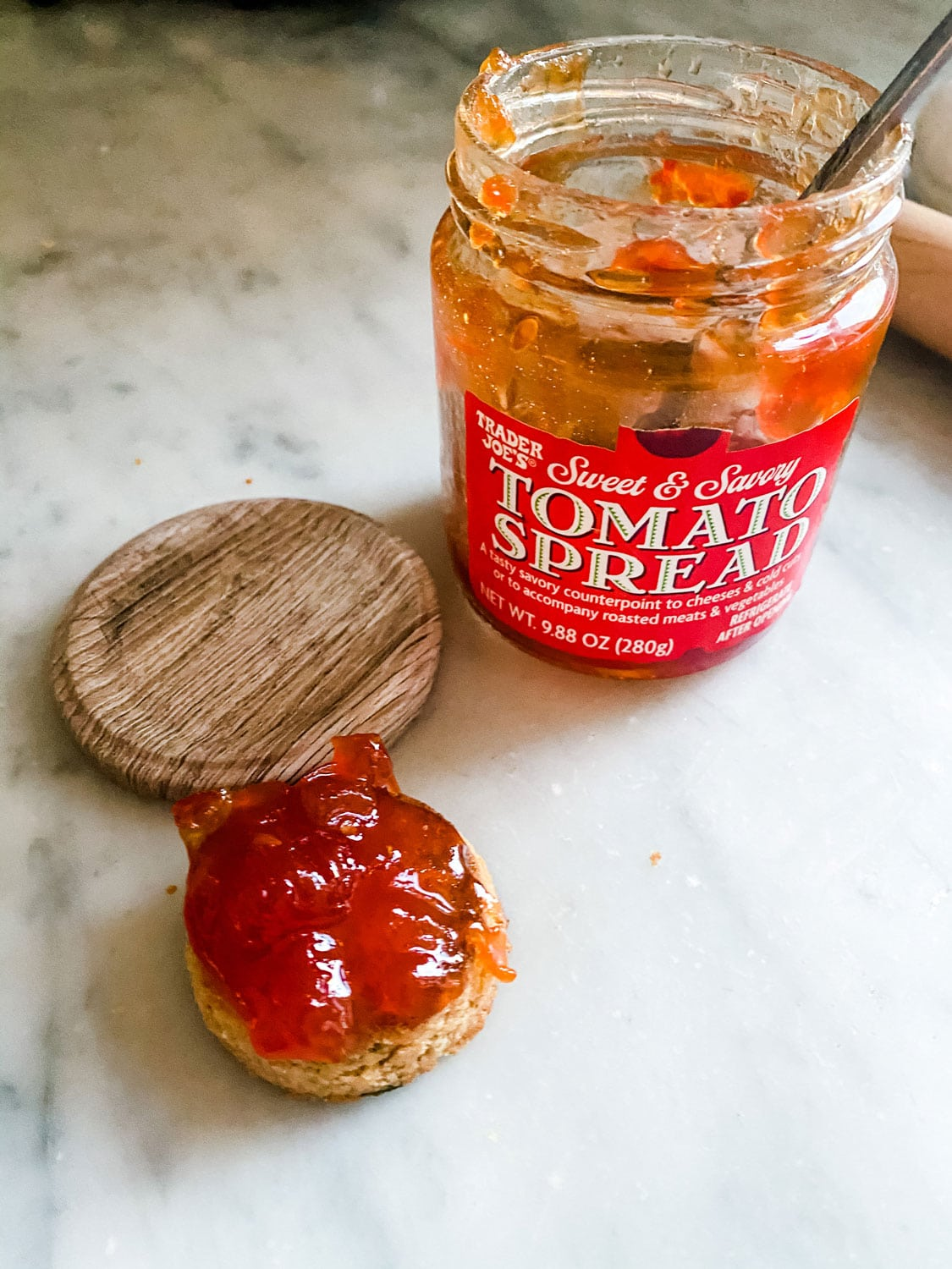 A jar of Trader Joe's tomato spread on a counter with a round cracker