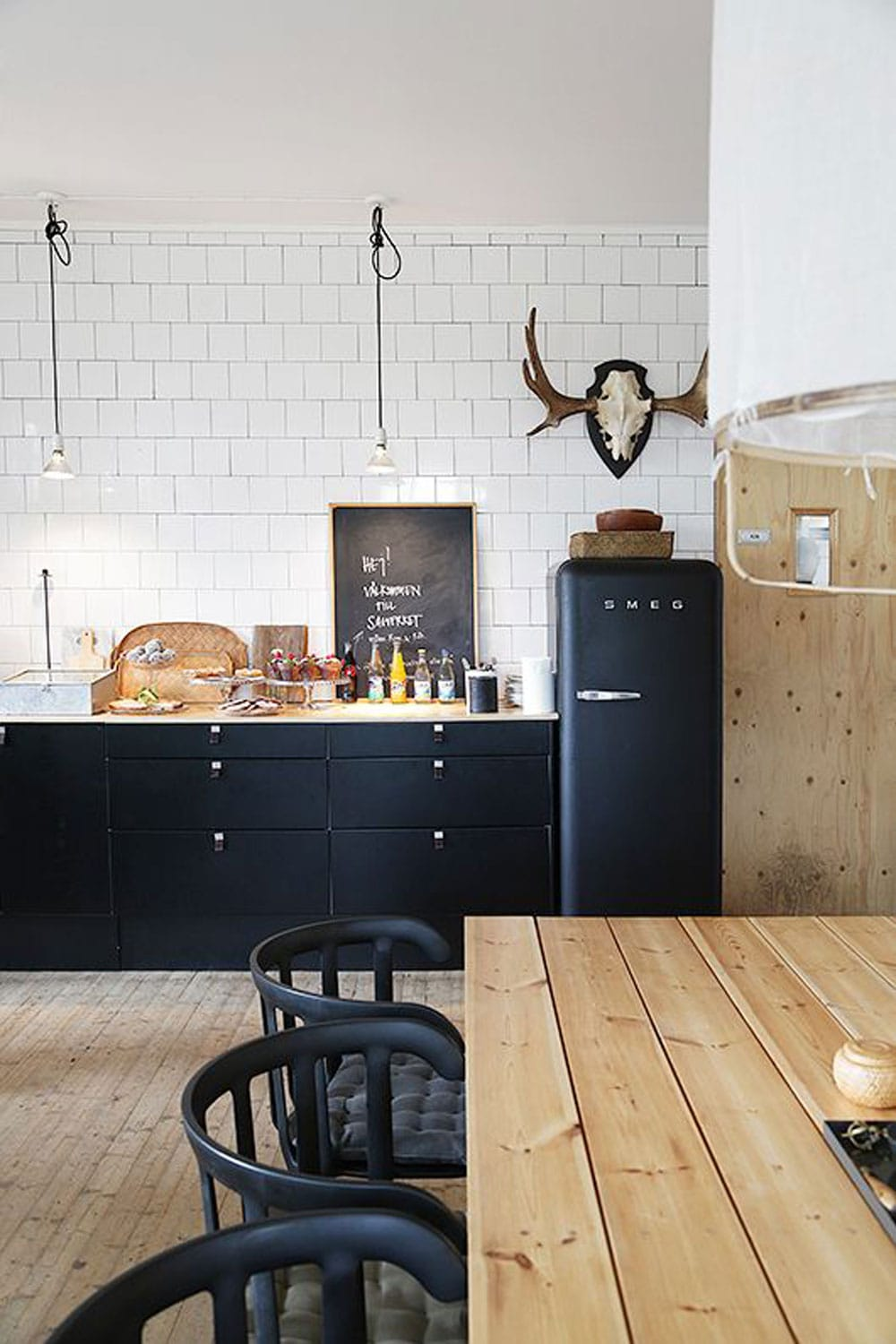 kitchen with black cabinets and Smeg with black chairs
