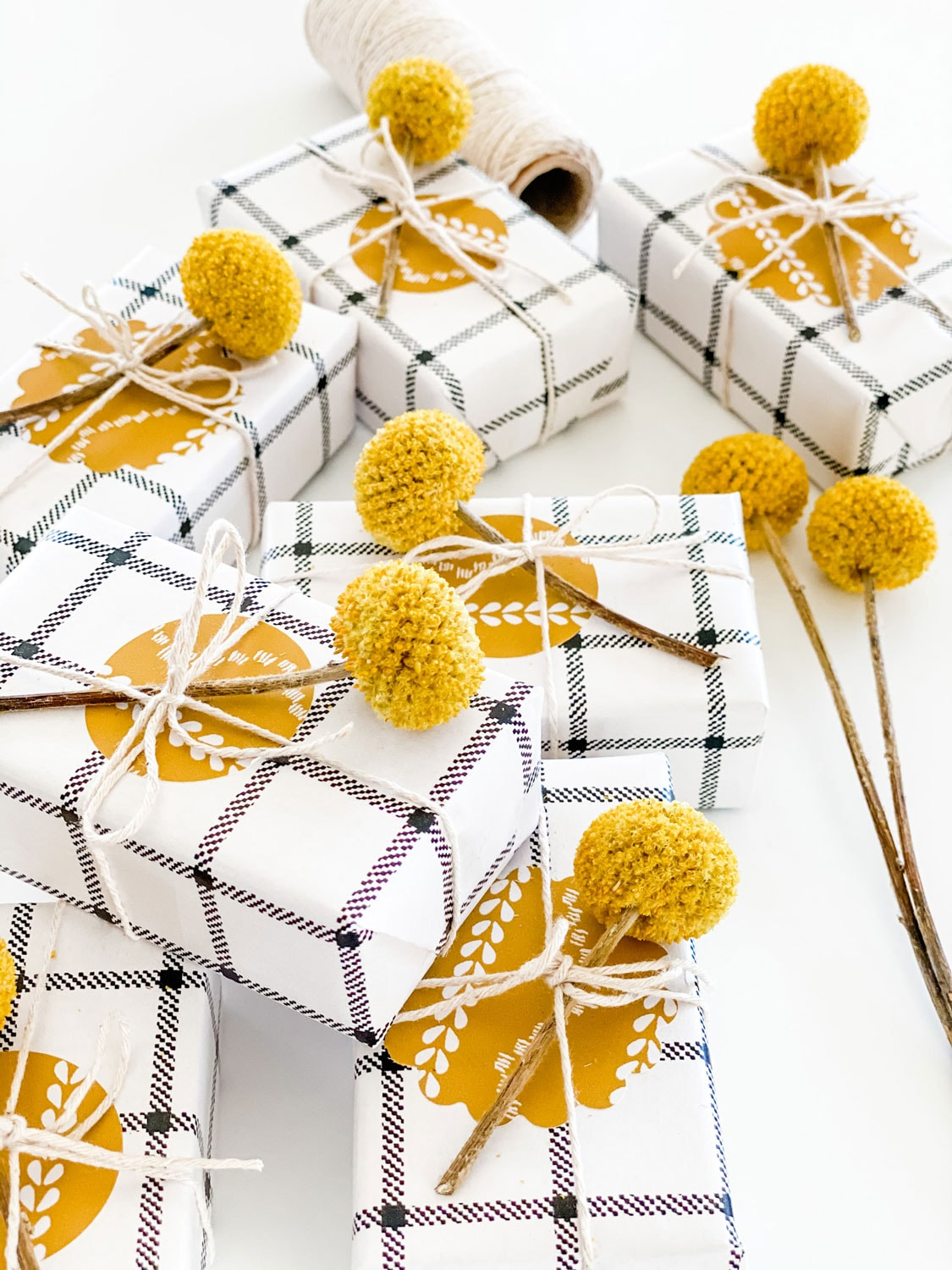 small wrapped gifts with gold wallpaper shapes and billy ball adorning package