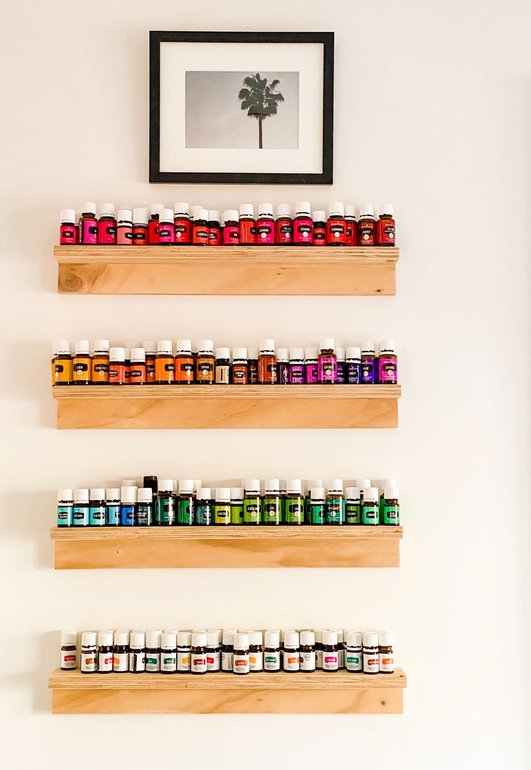 wood shelves on white wall with multi colored bottles of essential oils