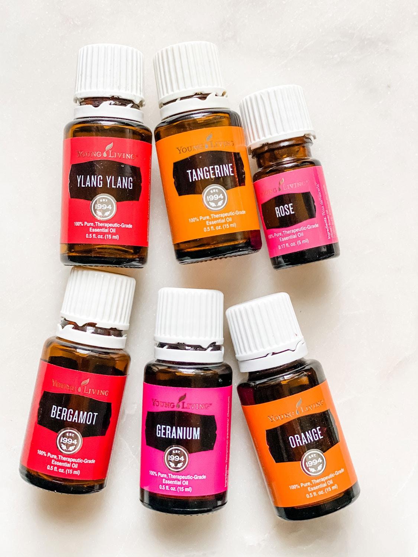 pink, orange, red essential oil bottles on white background