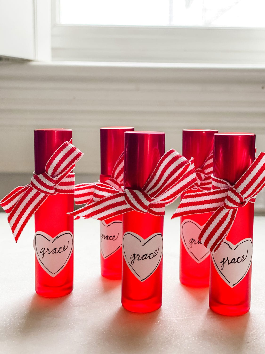 Red roller bottles with ribbon and heart shaped label