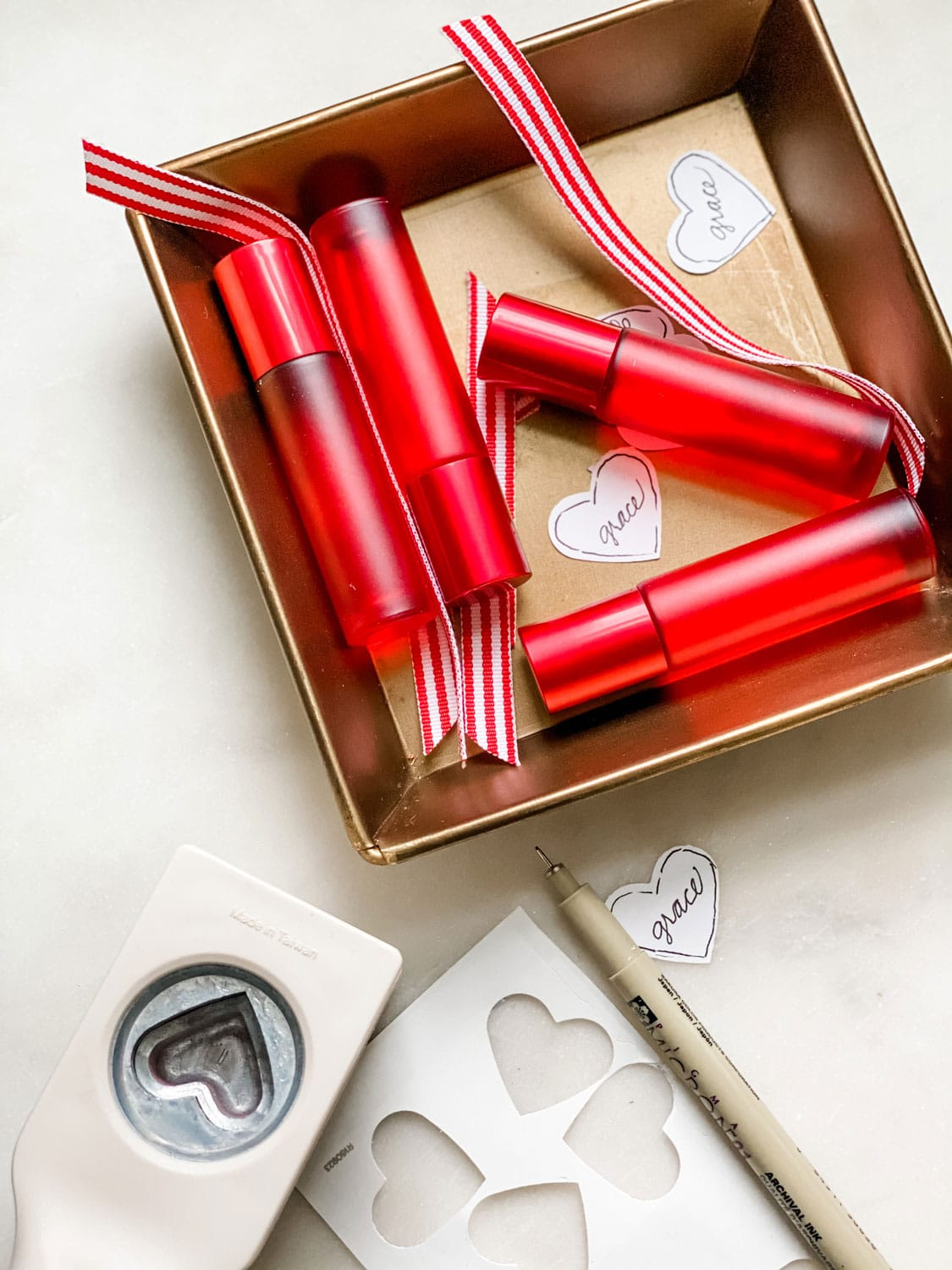 Red 10ml bottles on gold square tray with heart tags and heart punch, bits of striped ribbon
