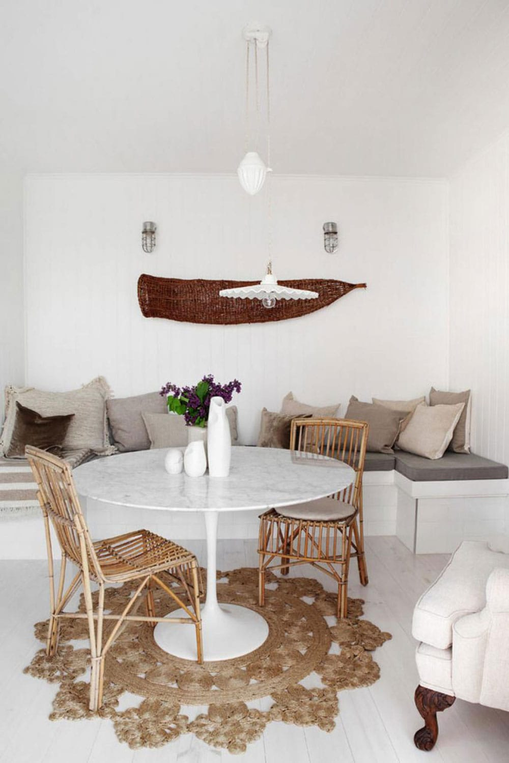 Saarinen table, round rug, banquette seating with pillows