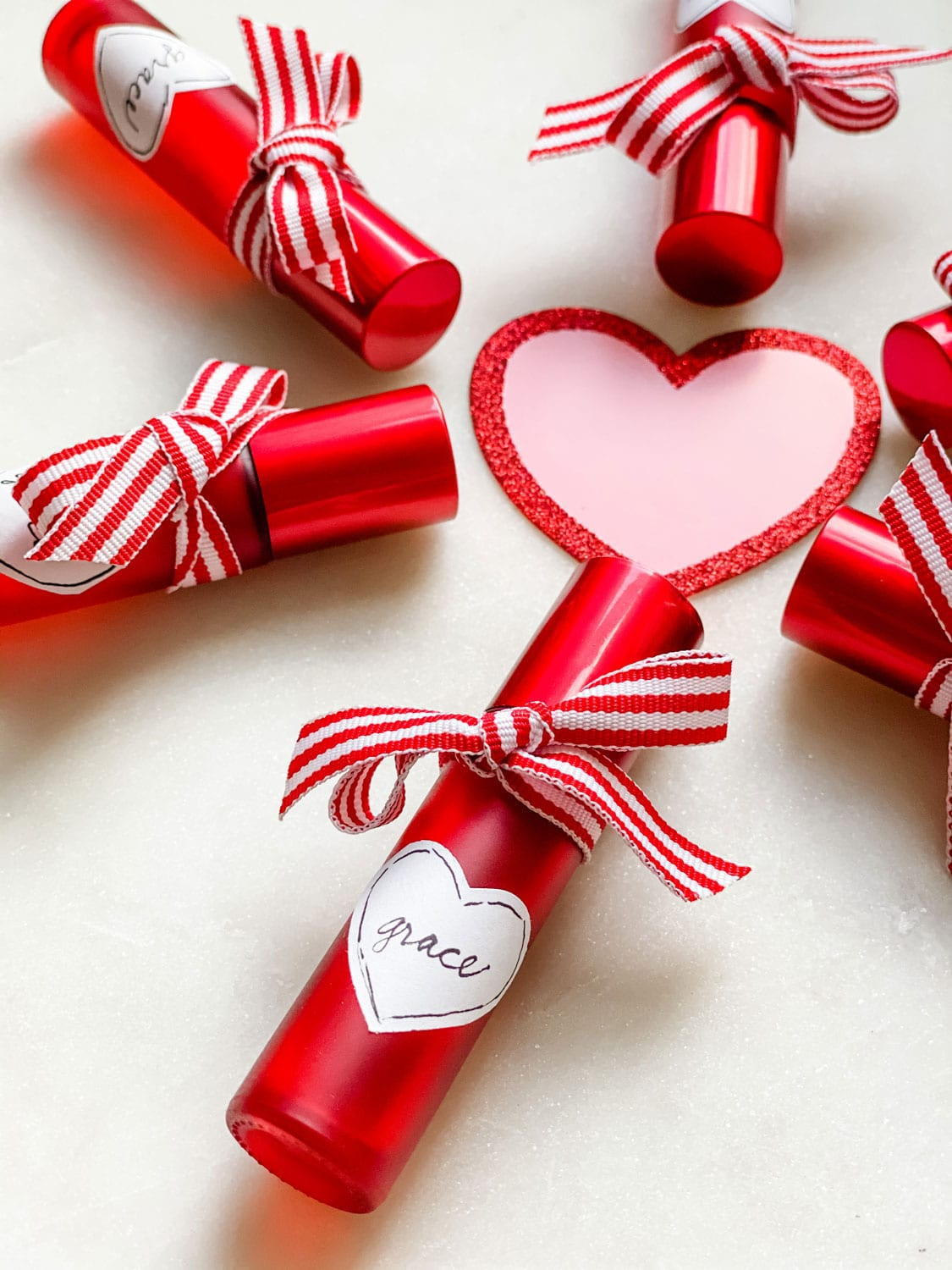 Red roller bottles with ribbon and heart shaped label around a pink/red glitter heart
