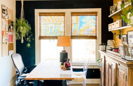 office with black wood wall, wallpaper on one wall and black rug, plants