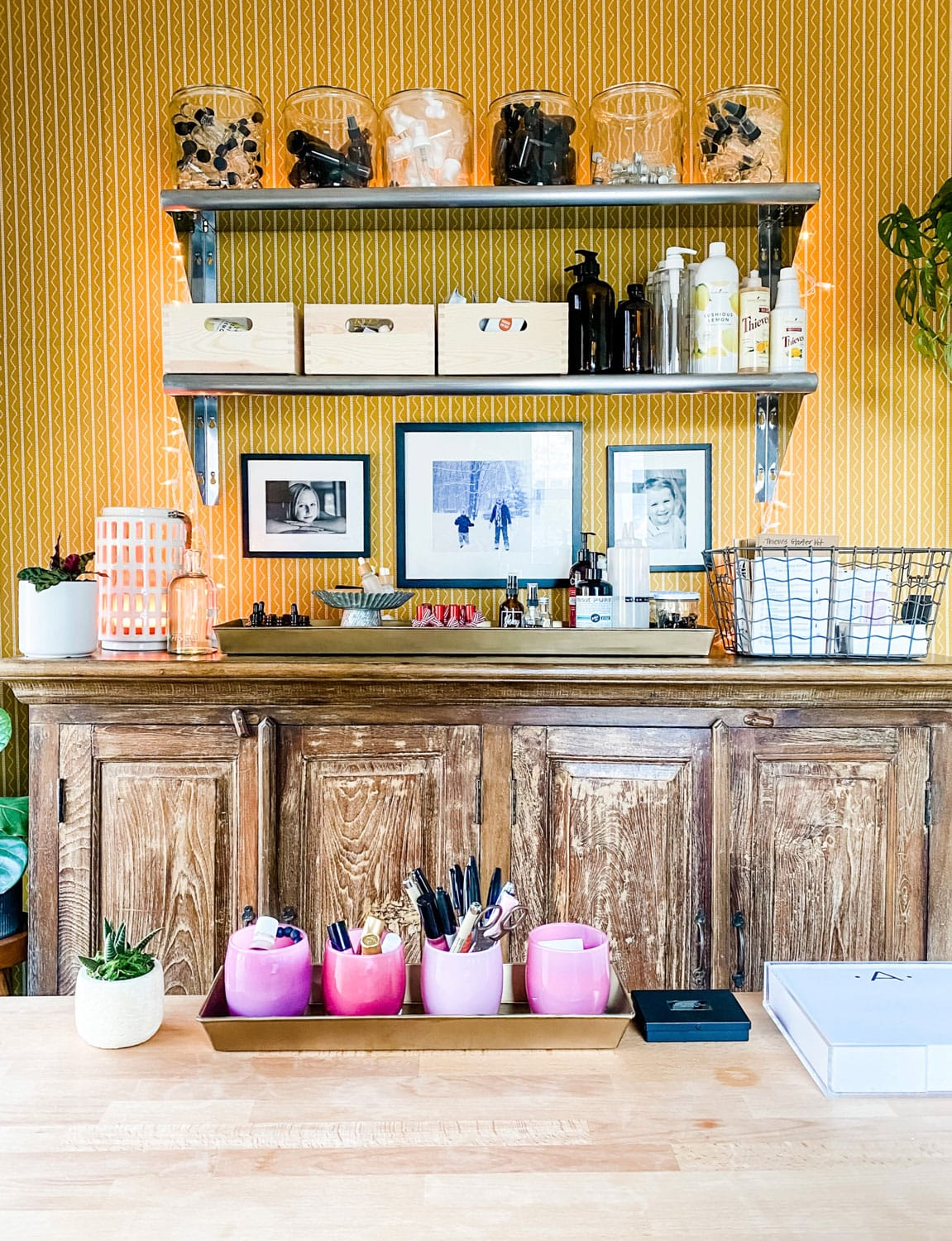 open shelving above wood hutch on wall with gold patterned wallpaper