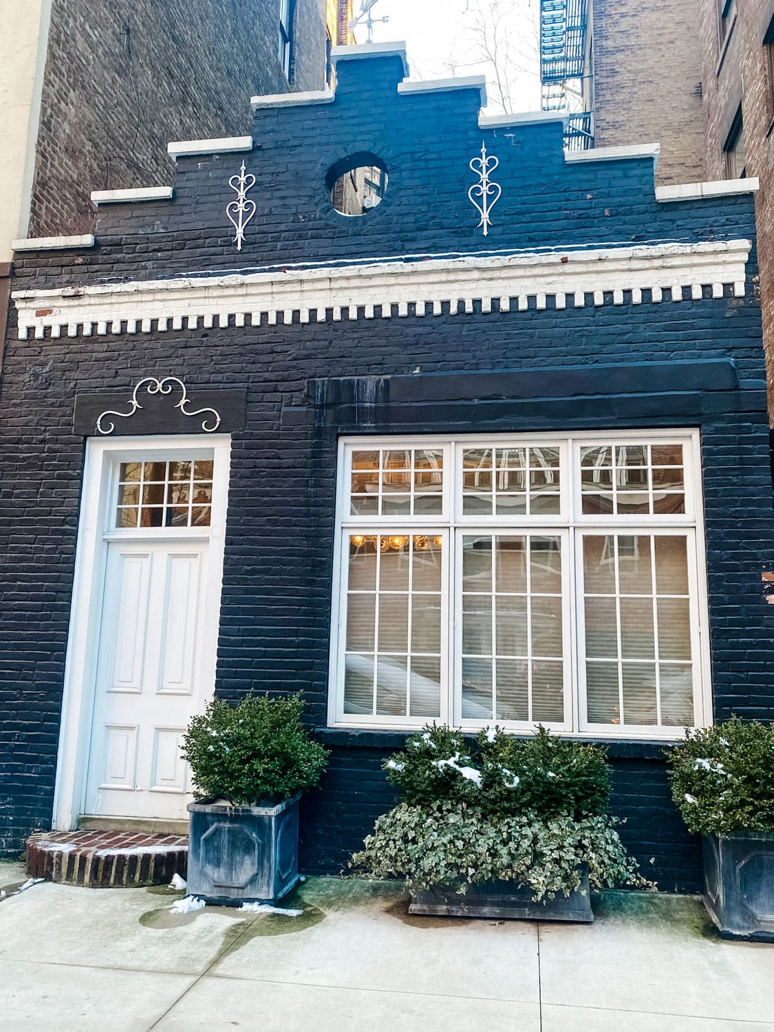 black painted brick house with white trim, boxwoods
