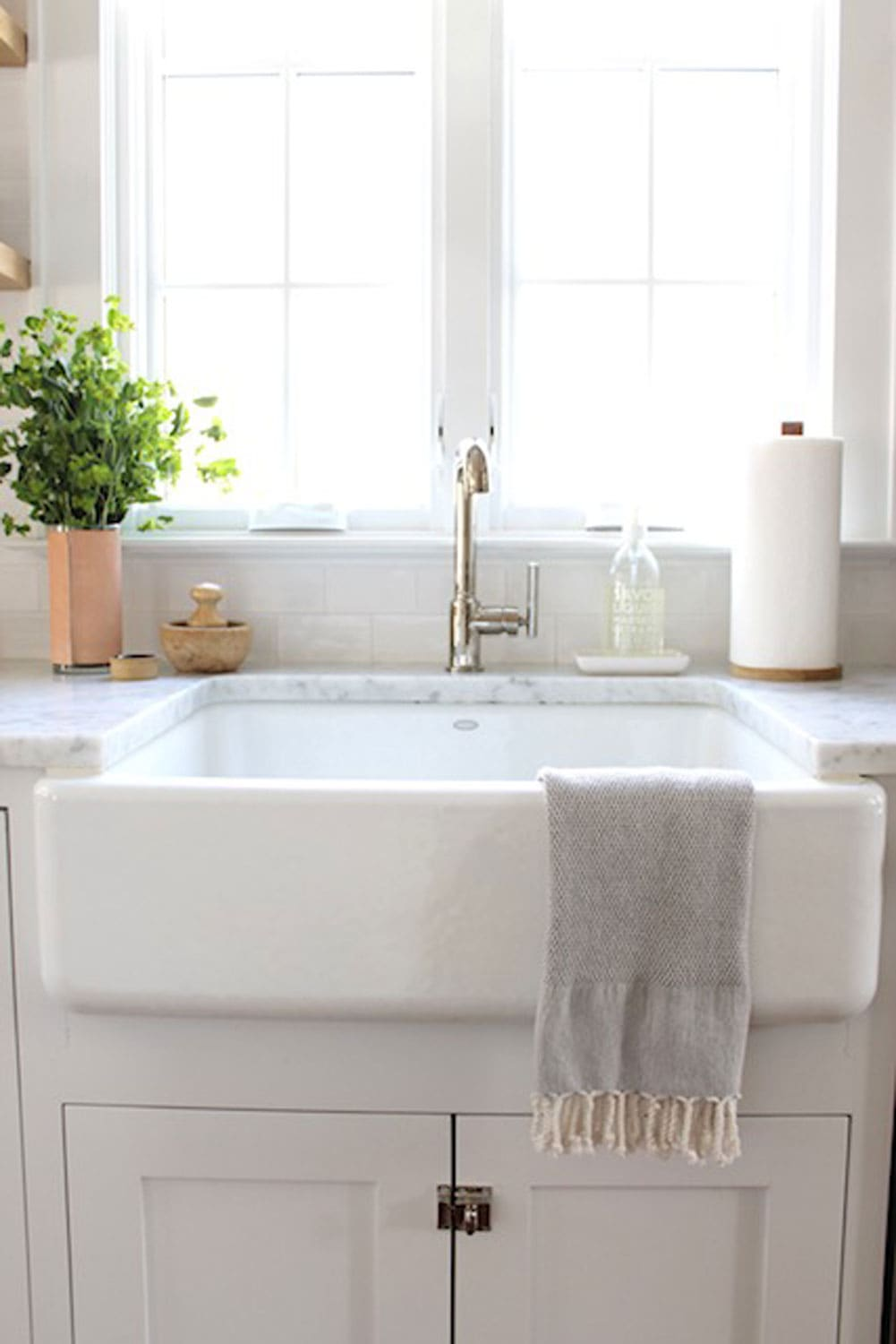 farm sink with leather vase with greens