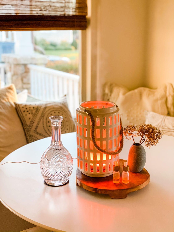 ceramic lantern, crystal decanter, round wood trivet on table