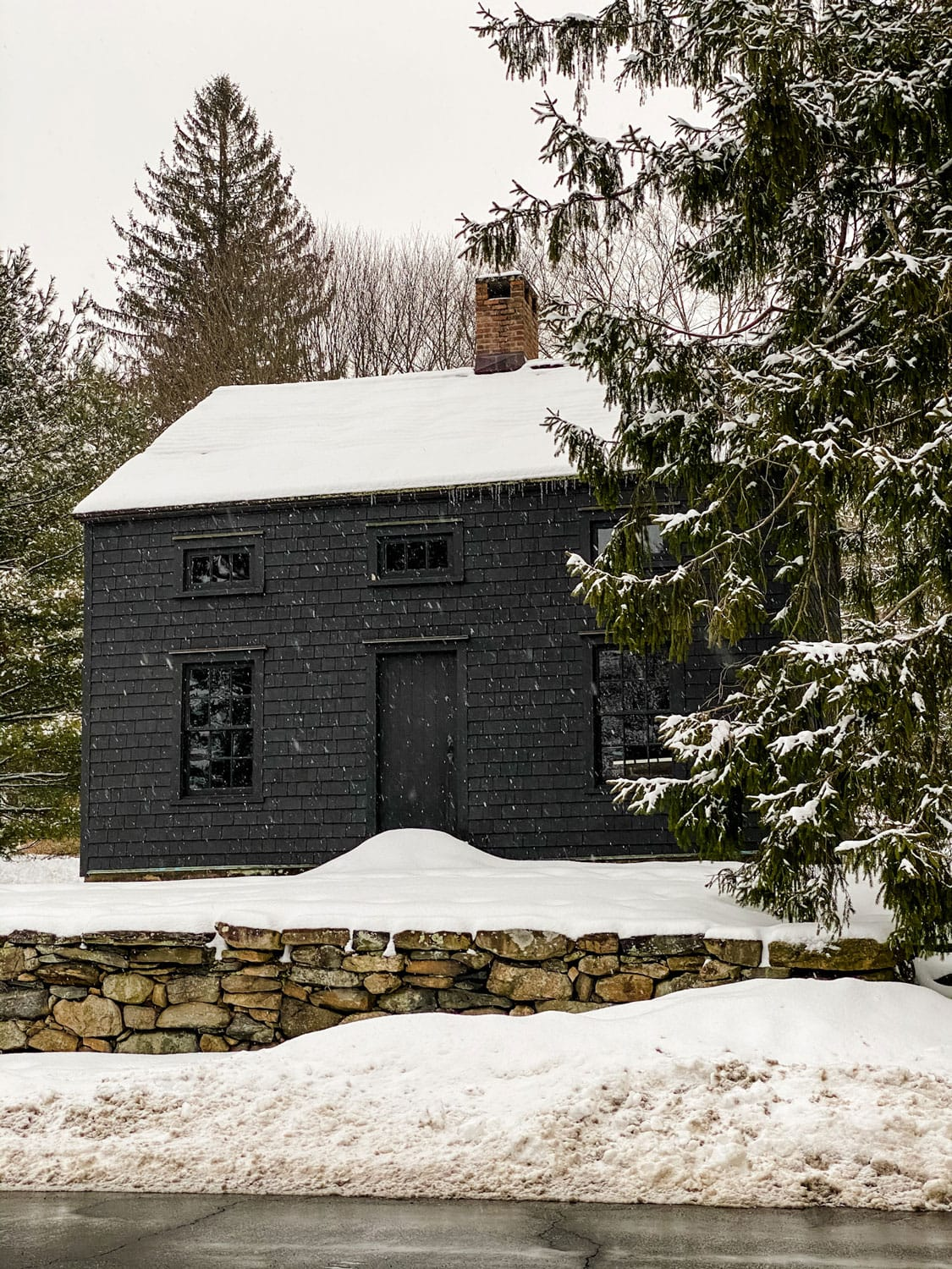 black house with stone wall, snow