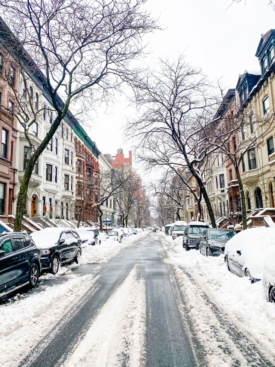 city street in the snow with brownstones
