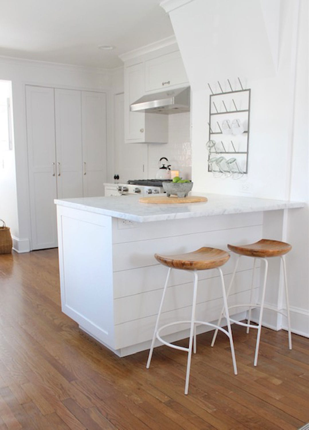 kitchen with all white, marble and wood and white stools