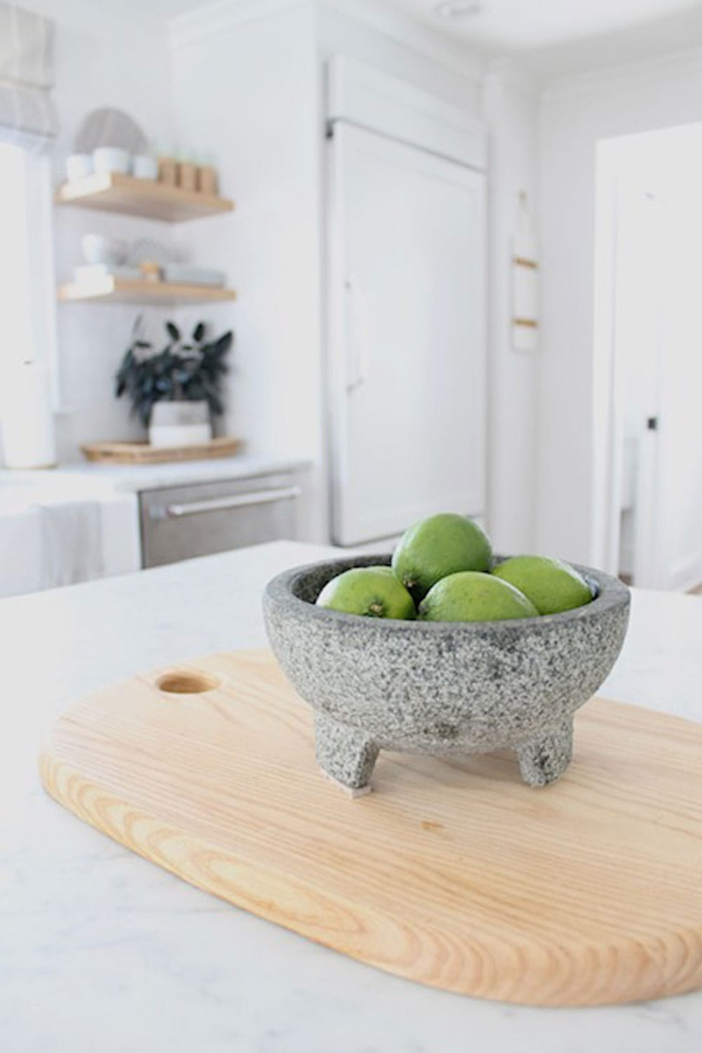 apples in stone bowl on wood ciutting board in white kitchen