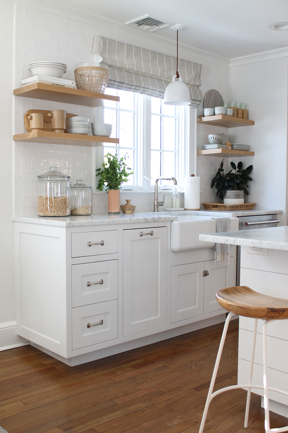 white kitchen with wood open shelves beside a farm sink