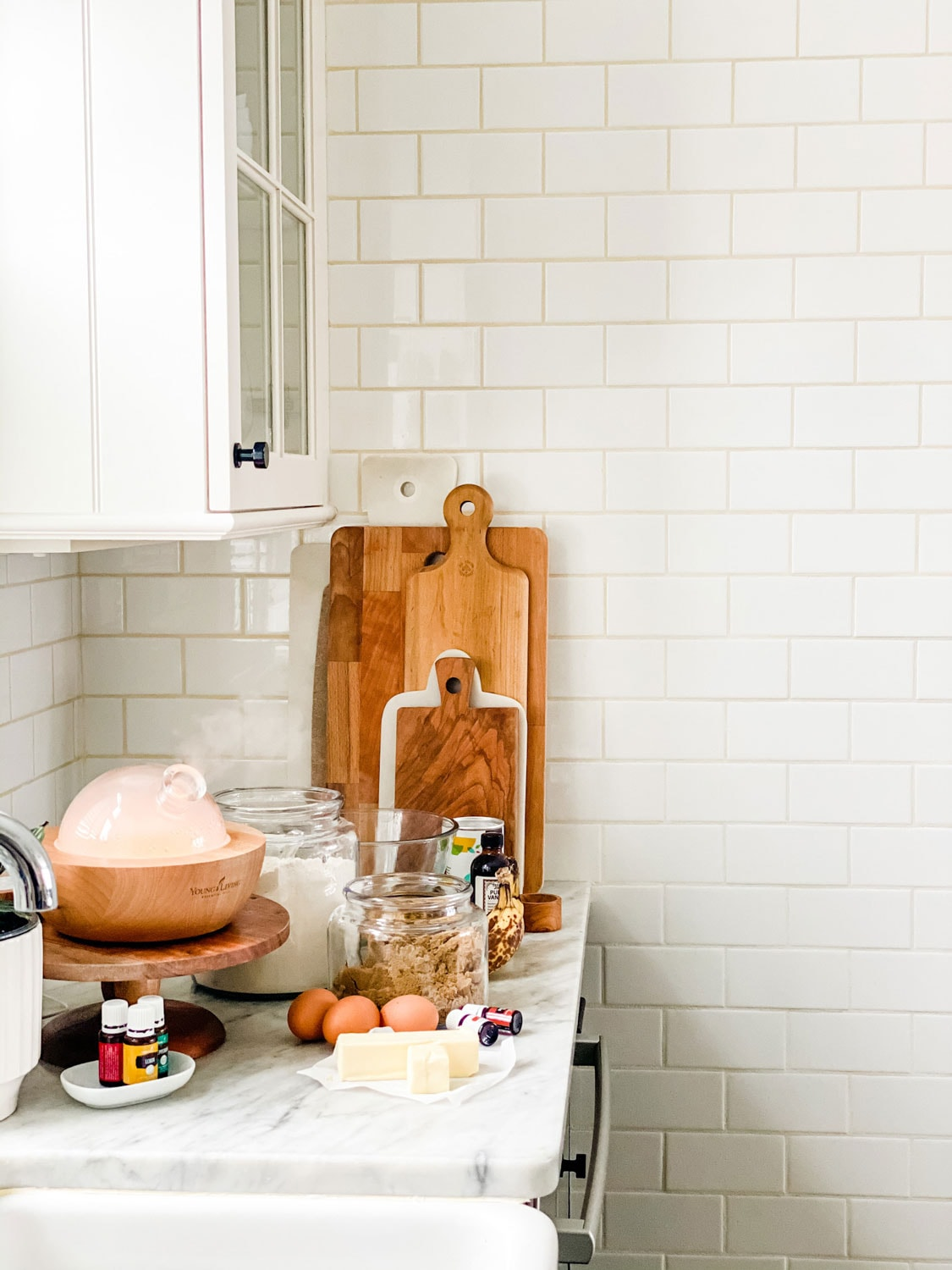 white kitchen with subway tile and baking supplies on the counter