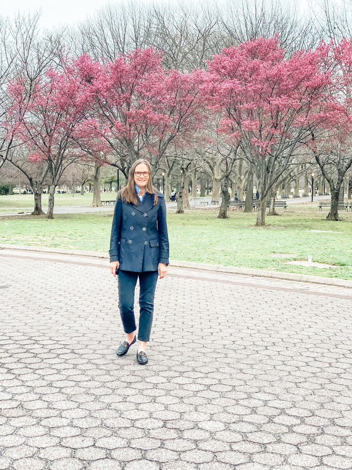 woman wearing black burberry in spring with pink flowering trees