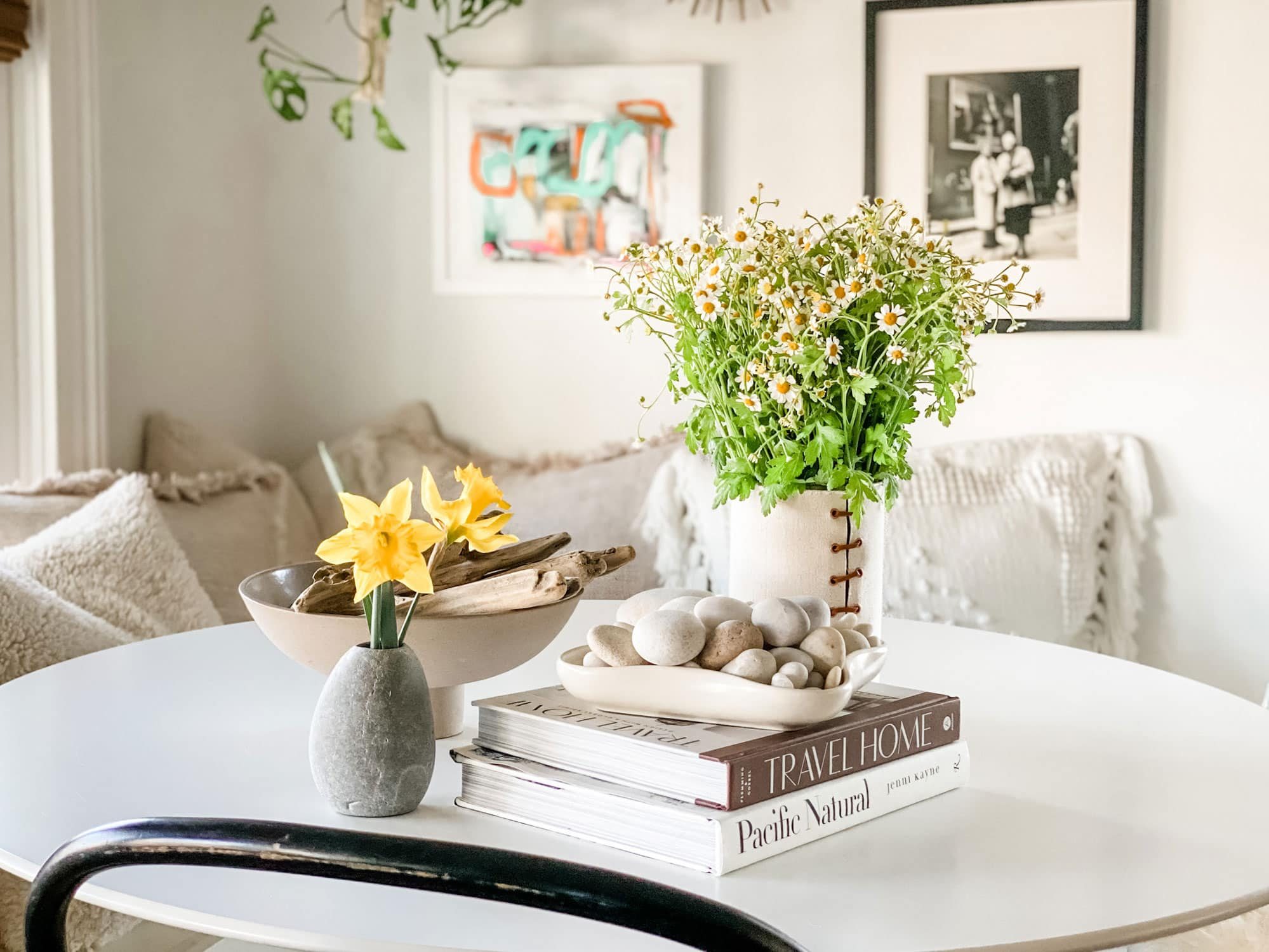 vase with chamomile, books and rocks/driftwood on white table