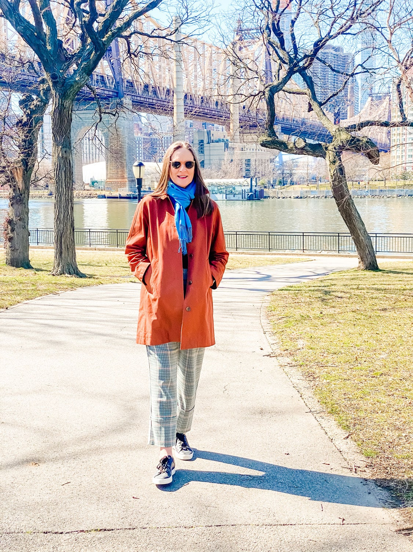woman wearing brown coat with bridge in background