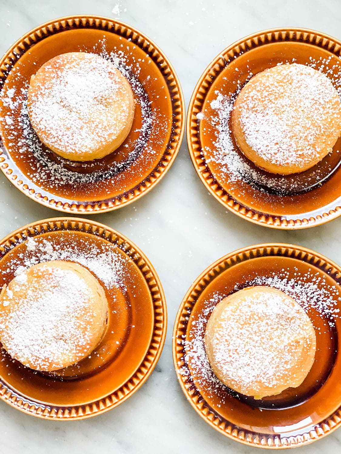 4 cakes dusted with powdered sugar on small gold plates