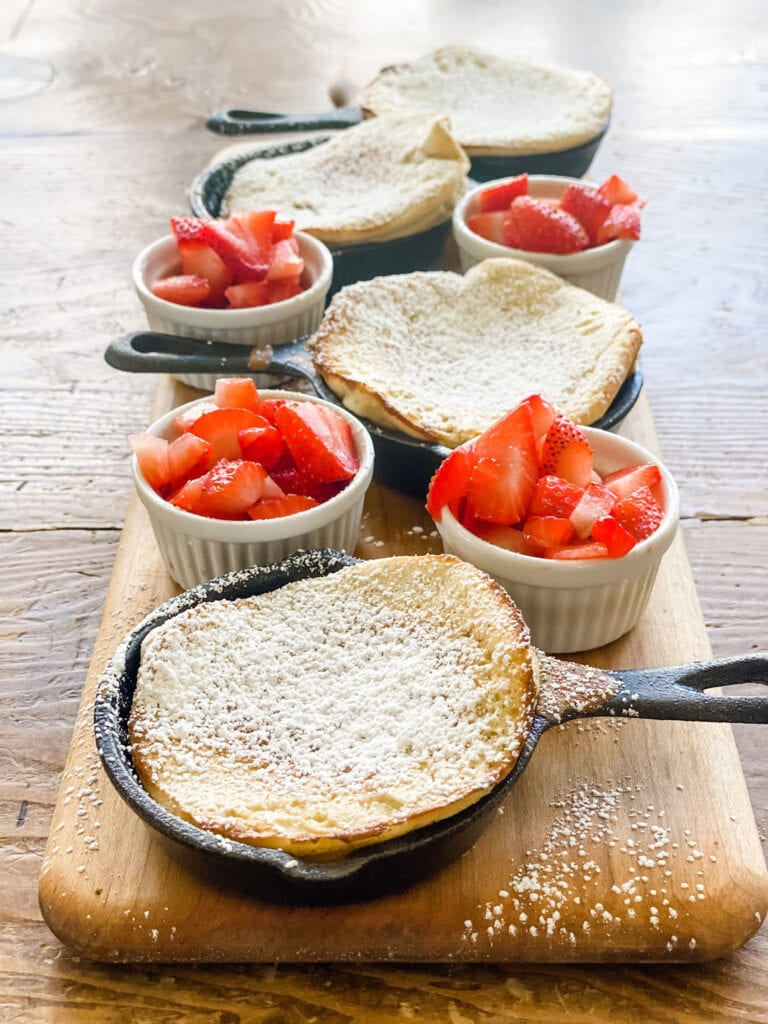 small cast iron pans with pancakes, ramekins with strawberries, on board