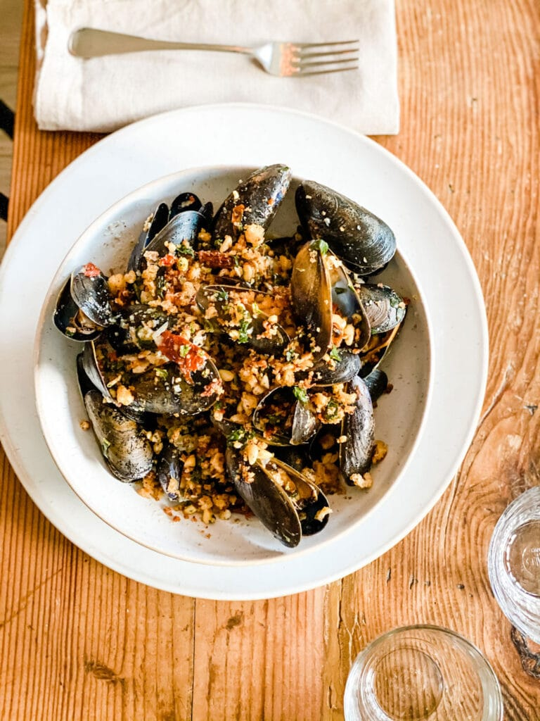 mussels in bowl on wood table