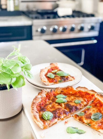 pizza in skillet with basil leaves and won pot holder and plates, basil plant