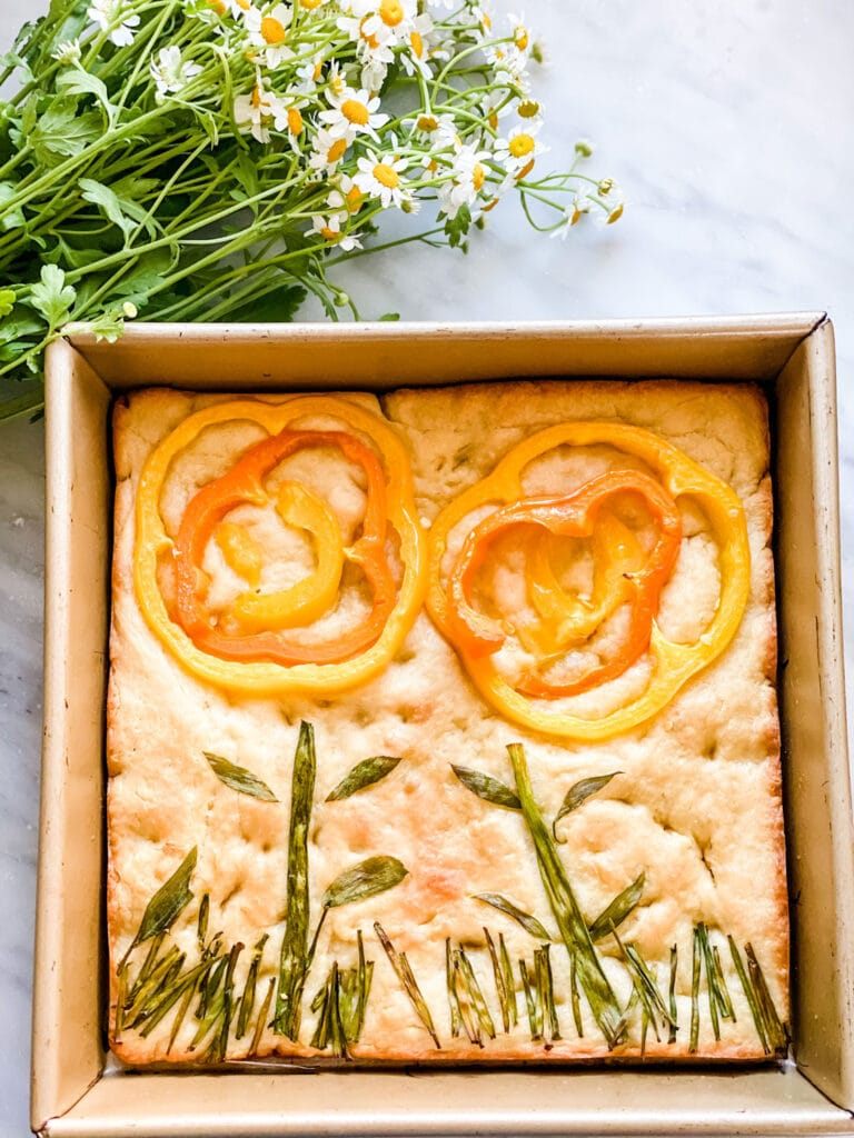 focaccia bread decorated with pepper and chives to look like flowers/grass