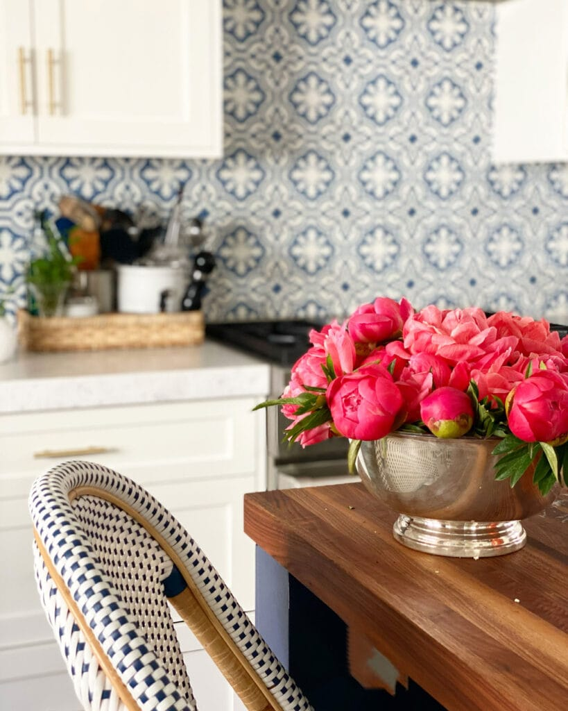 peonies on counter with stool and stove in background with blue and white patterned tile